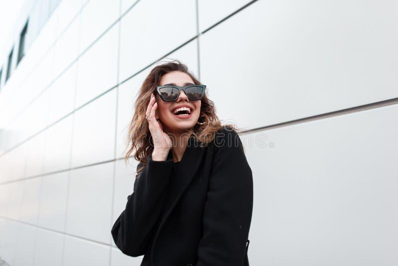Mujer joven feliz bonita del inconformista en una capa elegante negra en sonrisas de moda oscuras de las gafas de sol alrededor d fotos de archivo