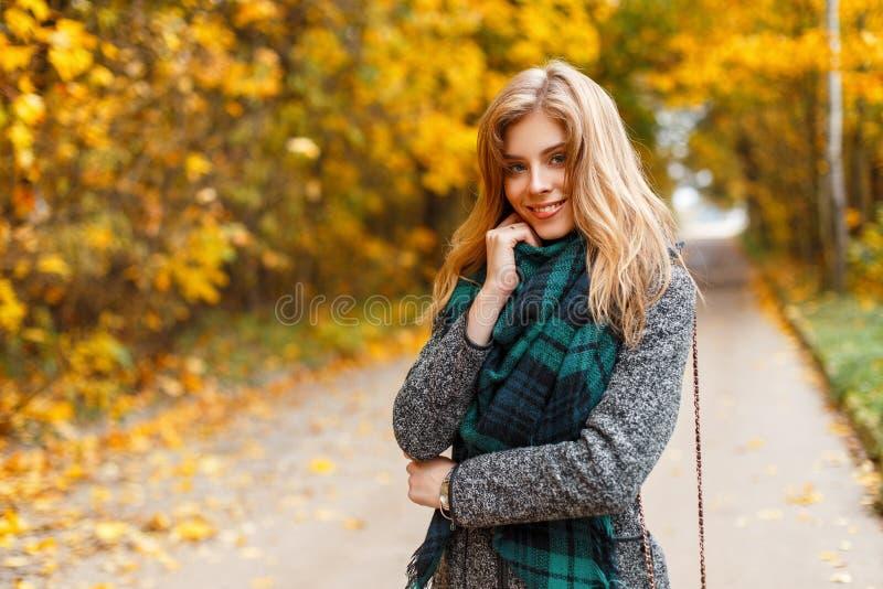 Mujer joven feliz bonita hermosa con sonrisa linda en bufanda verde del vintage en la capa gris de moda que presenta en parque de imagenes de archivo
