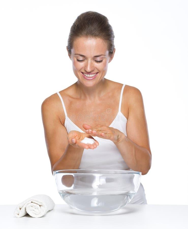 Mujer joven feliz con el bol de vidrio con las manos que se lavan del agua imágenes de archivo libres de regalías