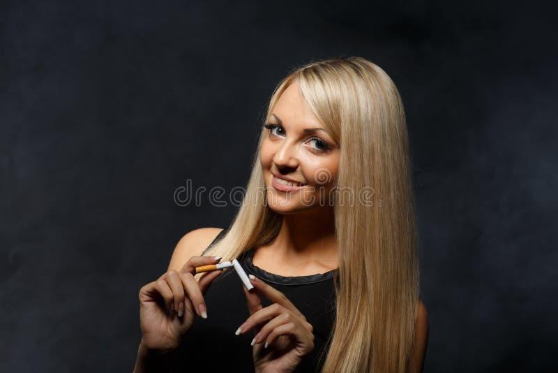 Mujer joven feliz con el cigarrillo quebrado foto de archivo