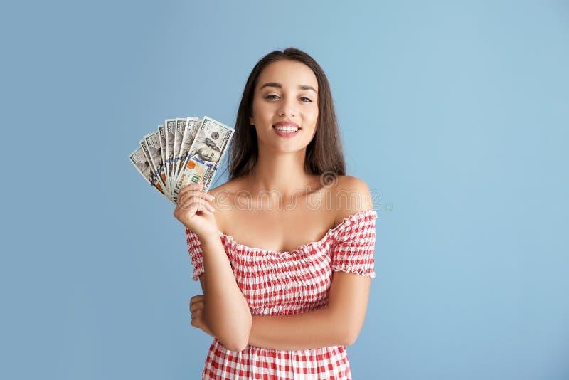 Mujer joven feliz con el dinero en fondo del color imagen de archivo
