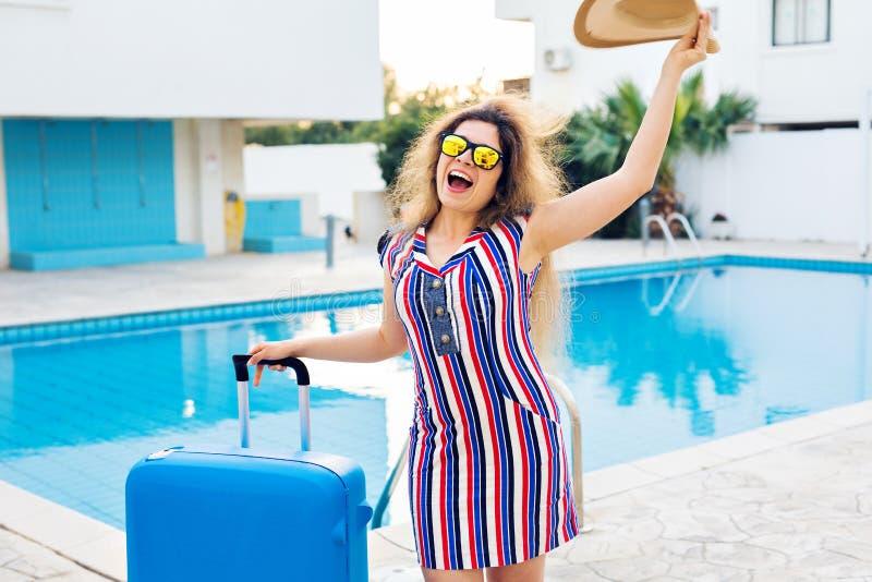 Mujer joven feliz con el equipaje azul que llega al centro turístico Ella está caminando al lado de la piscina Principio de fotografía de archivo