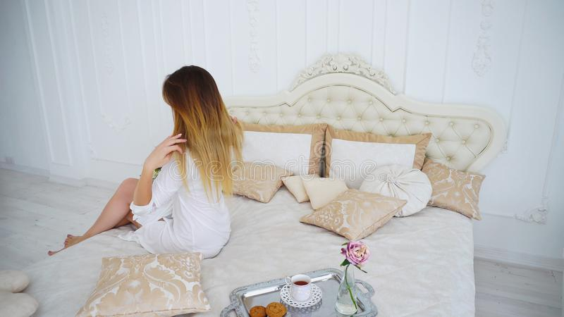 Mujer joven feliz con el estado del pelo, sentándose con de nuevo a la cámara en cama suave fotos de archivo libres de regalías