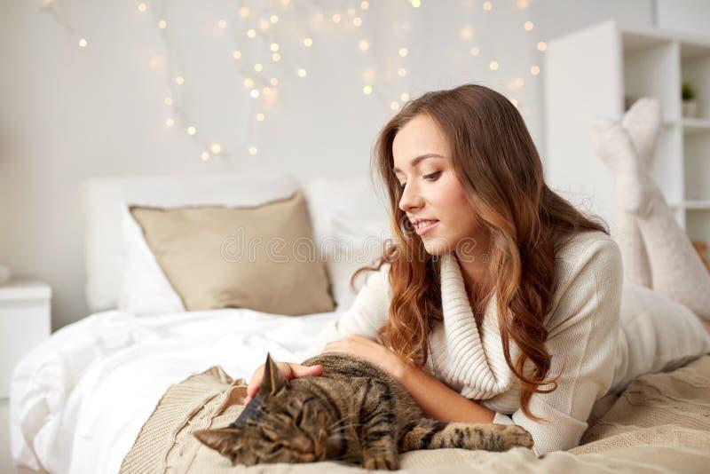 Mujer joven feliz con el gato que miente en cama en casa foto de archivo libre de regalías