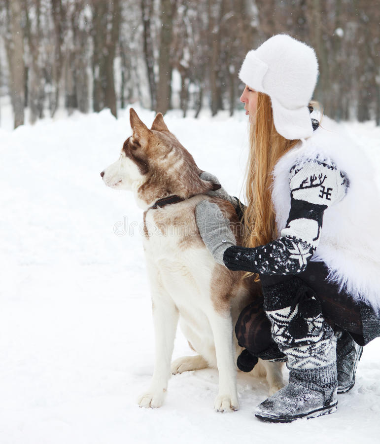 Mujer joven feliz con el perro de los perros esquimales fotografía de archivo