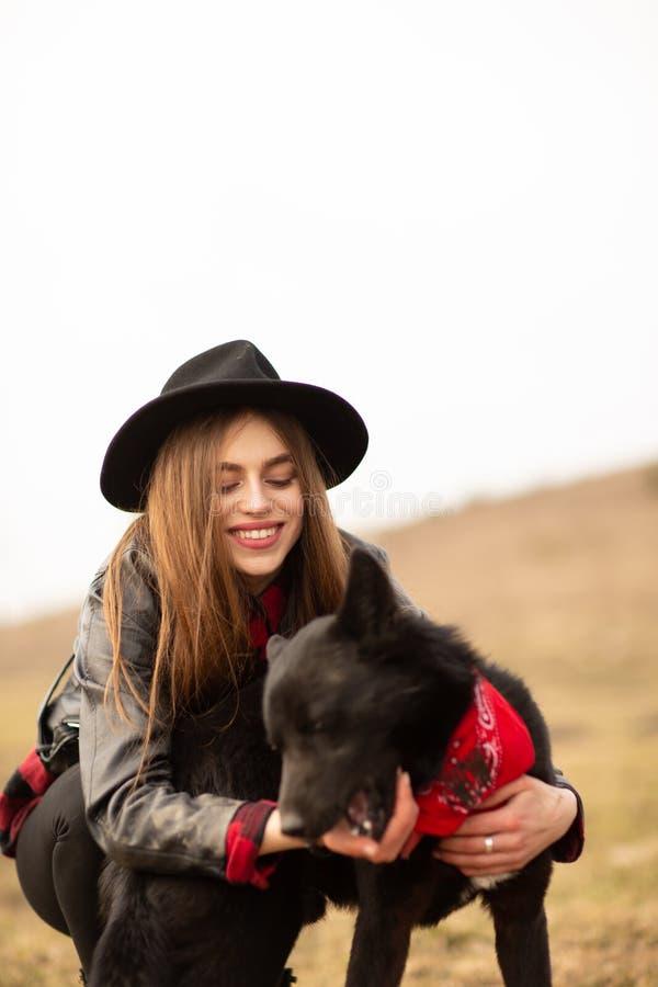 Mujer joven feliz con el sombrero negro, plaing con su perro negro en la orilla del lago foto de archivo libre de regalías