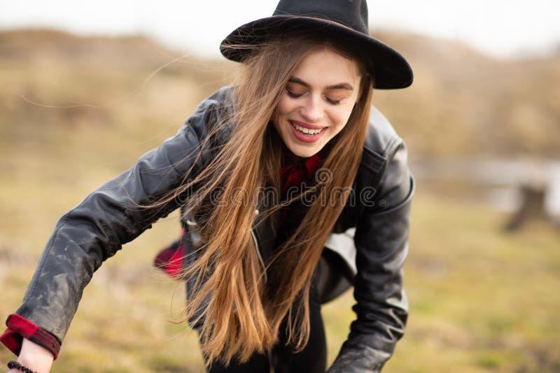 Mujer joven feliz con el sombrero negro, plaing con su perro negro en la orilla del lago imagenes de archivo