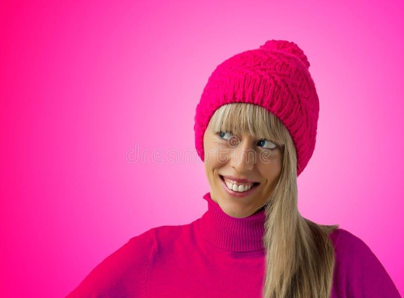 Mujer joven feliz con el sombrero rosado del invierno fotos de archivo libres de regalías