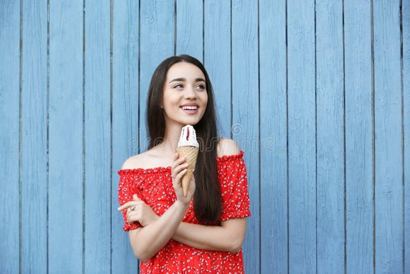 Mujer joven feliz con helado delicioso en cono de la galleta cerca de la pared de madera fotos de archivo