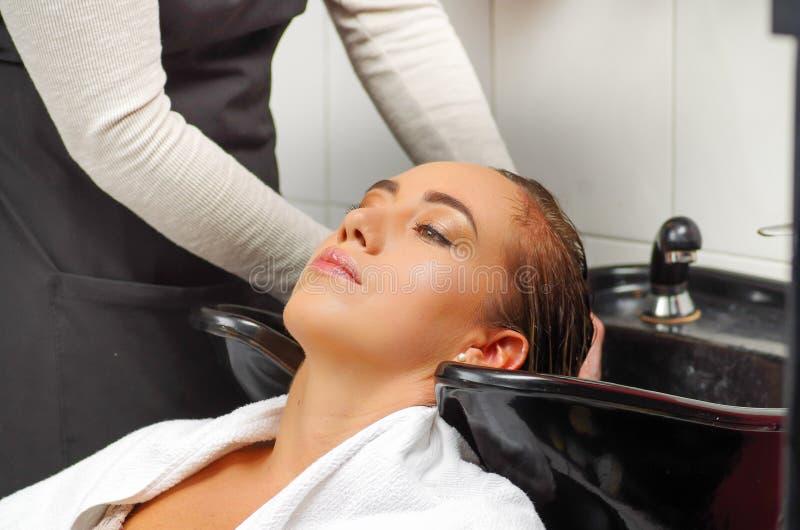 Mujer joven feliz con la cabeza que se lava del peluquero en el salón de pelo imagen de archivo libre de regalías