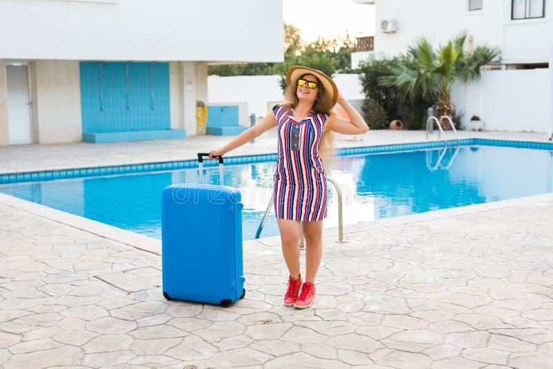 Mujer joven feliz con la maleta azul que llega al centro turístico Ella está caminando al lado de la piscina Principio de imagen de archivo libre de regalías