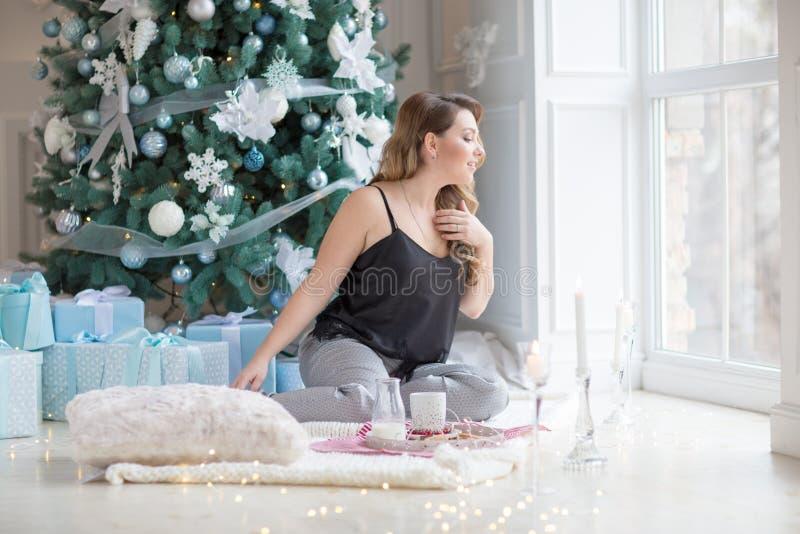 Mujer joven feliz con la mirada a la mañana de la Navidad de la ventana del invierno imagenes de archivo