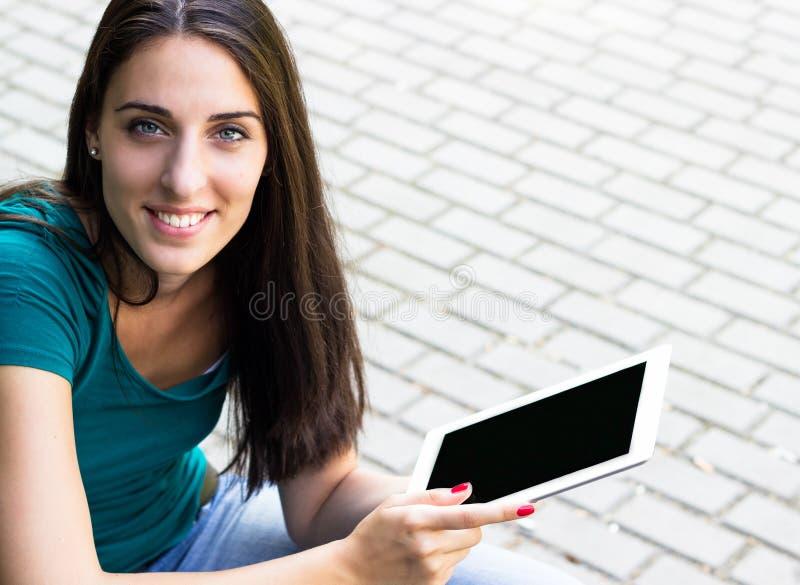Mujer joven feliz con la tableta digital en la ciudad imágenes de archivo libres de regalías