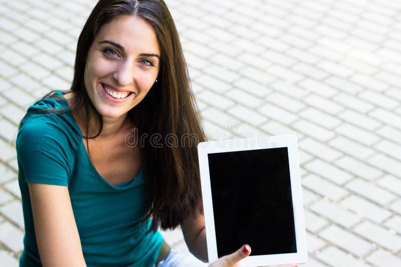 Mujer joven feliz con la tableta digital en la ciudad foto de archivo