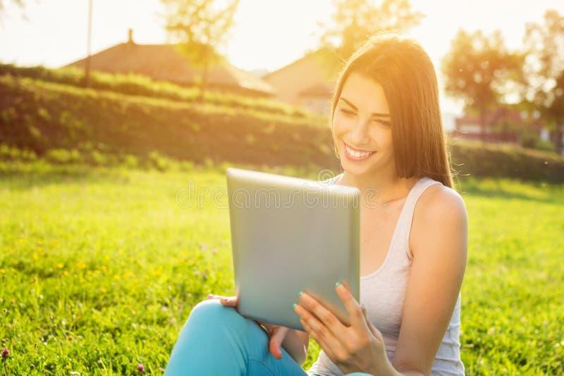 Mujer joven feliz con la tableta en parque en día de verano soleado fotos de archivo