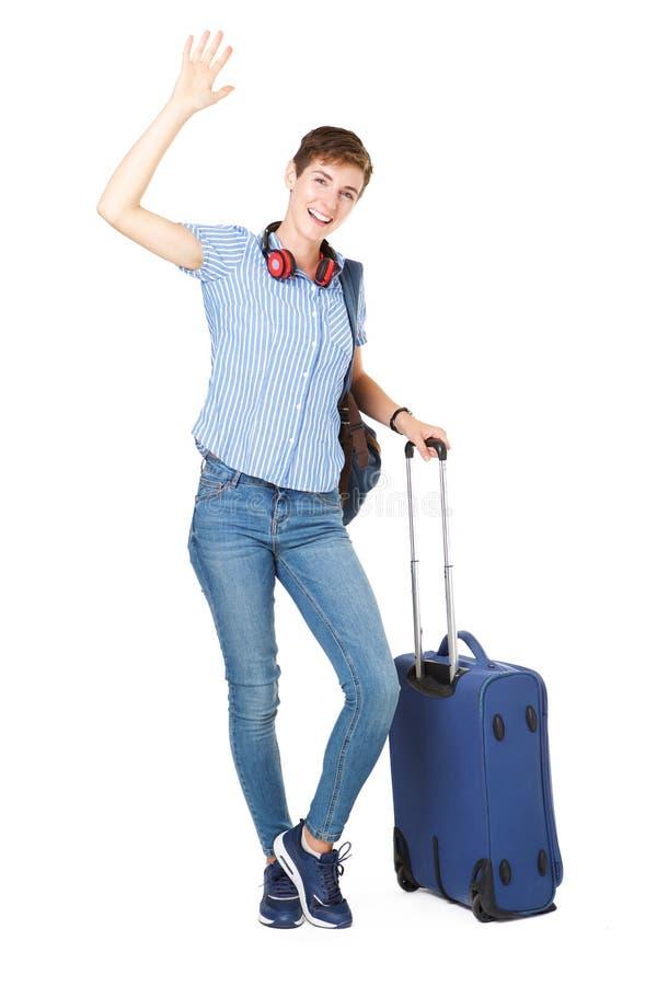 Mujer joven feliz con los bolsos del viaje que agitan su mano hola fotos de archivo