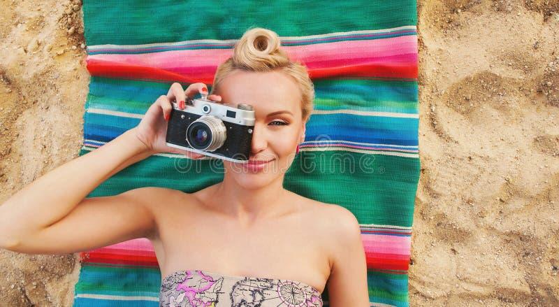 Mujer joven feliz con los detalles coloridos que mienten en la playa y el t imagen de archivo libre de regalías