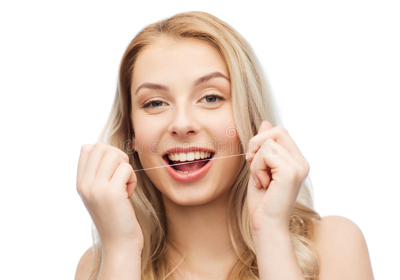 Mujer joven feliz con los dientes de la limpieza de la seda dental fotos de archivo libres de regalías