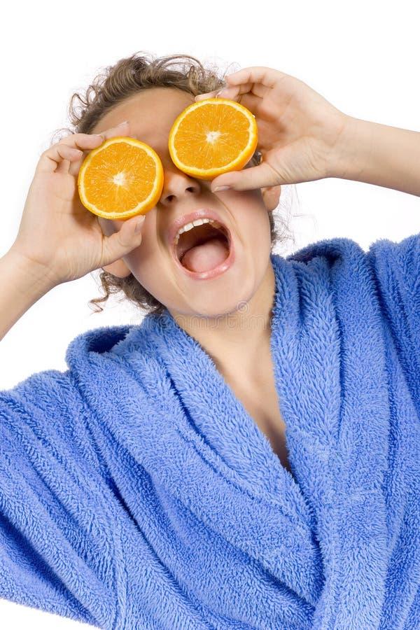 Mujer joven feliz con los halfs de la naranja foto de archivo