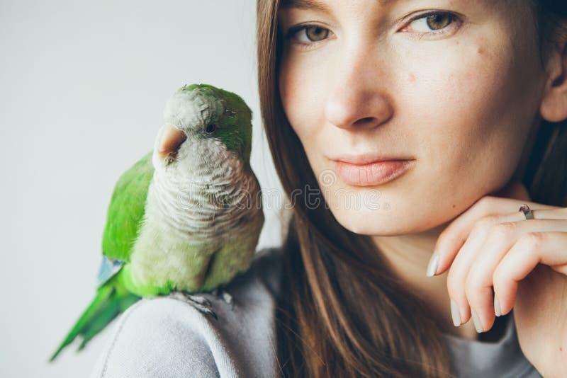 Mujer joven feliz con los ojos verdes y el loro verde que se sientan en su hombro foto de archivo