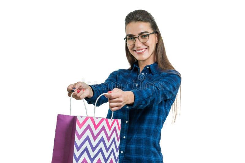 Mujer joven feliz con un panier, en el fondo blanco, hembra hermosa en vidrios con una sonrisa blanca perfecta imagenes de archivo