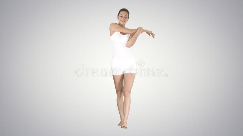 Mujer joven feliz contenta que estira sus brazos mientras que camina en fondo de la pendiente foto de archivo
