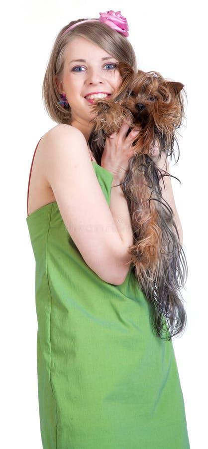 Mujer joven feliz de la belleza en alineada verde con el perro fotografía de archivo libre de regalías