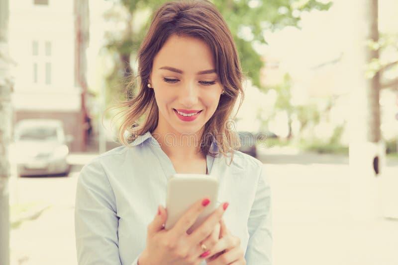 Mujer joven feliz de la ciudad que usa el teléfono móvil imagenes de archivo