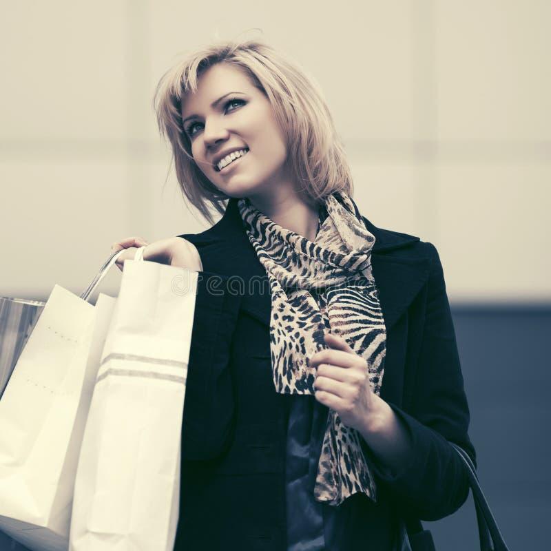 Mujer joven feliz de la moda con los bolsos de compras en calle de la ciudad fotografía de archivo