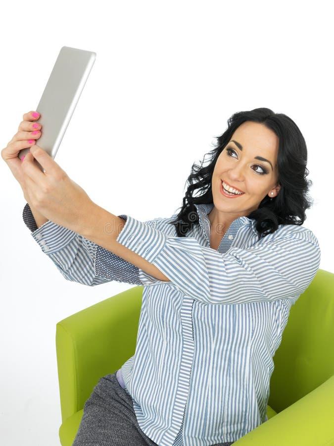 Mujer joven feliz de la vena atractiva que usa una tableta que toma un autorretrato foto de archivo
