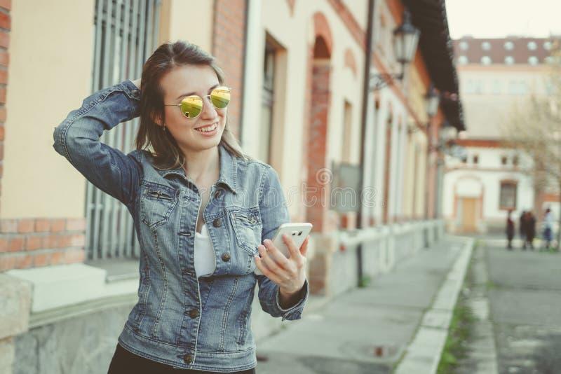 Mujer joven feliz del inconformista que camina en la calle, usando su smartphone imagen de archivo