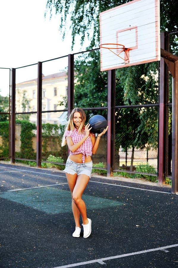 Mujer joven feliz del retrato que lleva a cabo baloncesto en corte al aire libre imagen de archivo libre de regalías