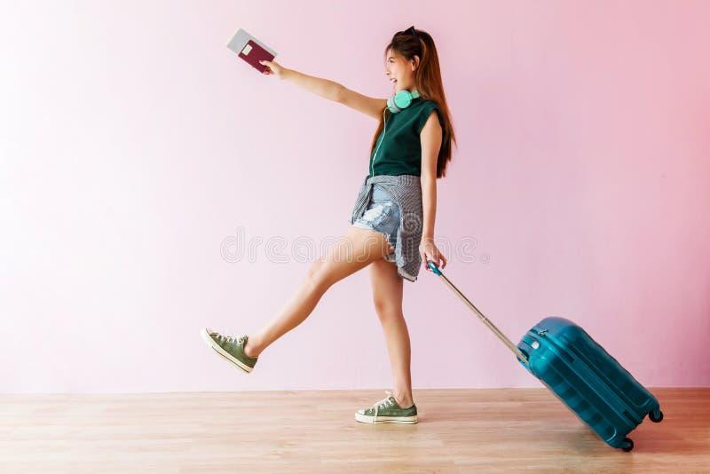 Mujer joven feliz del viajero que camina con la maleta y la música Headp fotos de archivo