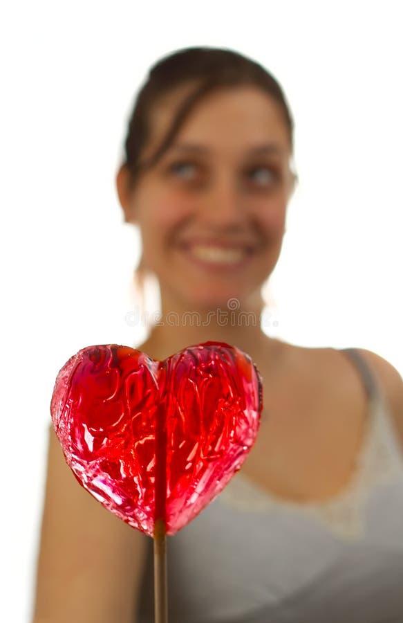 Mujer joven feliz detrás del lollipop en forma de corazón fotografía de archivo