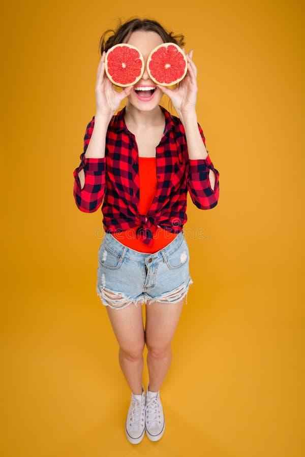 Mujer joven feliz divertida con mitades del pomelo sobre ojos imagenes de archivo