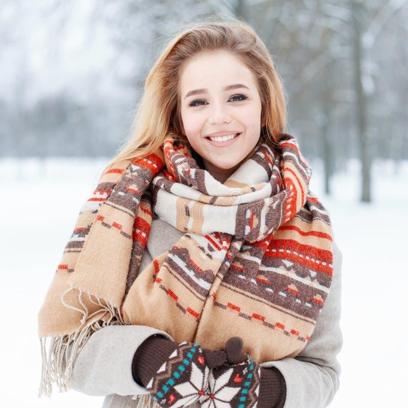 Mujer joven feliz divertida con sonrisa hermosa en ropa elegante del invierno en el fondo del árboles nevosos en el parque Muchac imagen de archivo