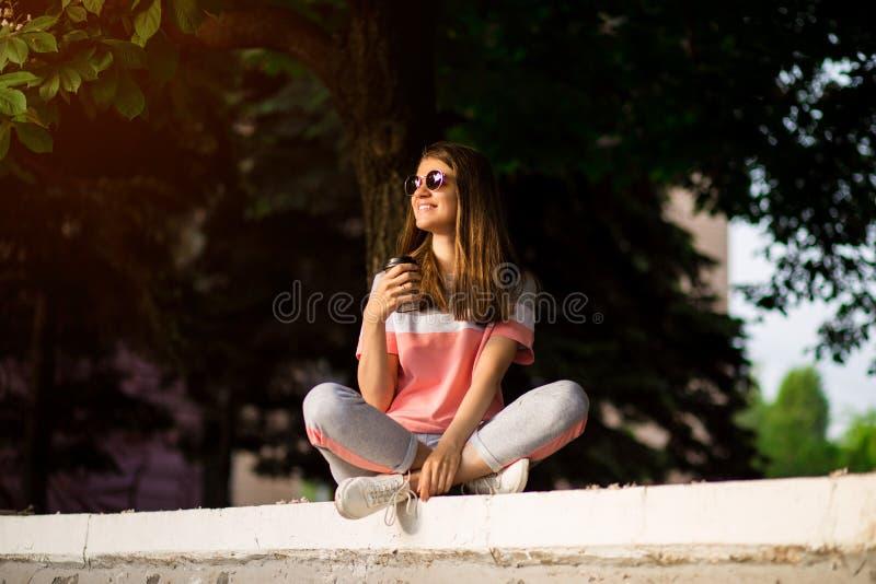 Mujer joven feliz elegante en las gafas de sol, zapatillas de deporte blancas Ella sostiene el caf? para ir Retrato de la muchach foto de archivo libre de regalías