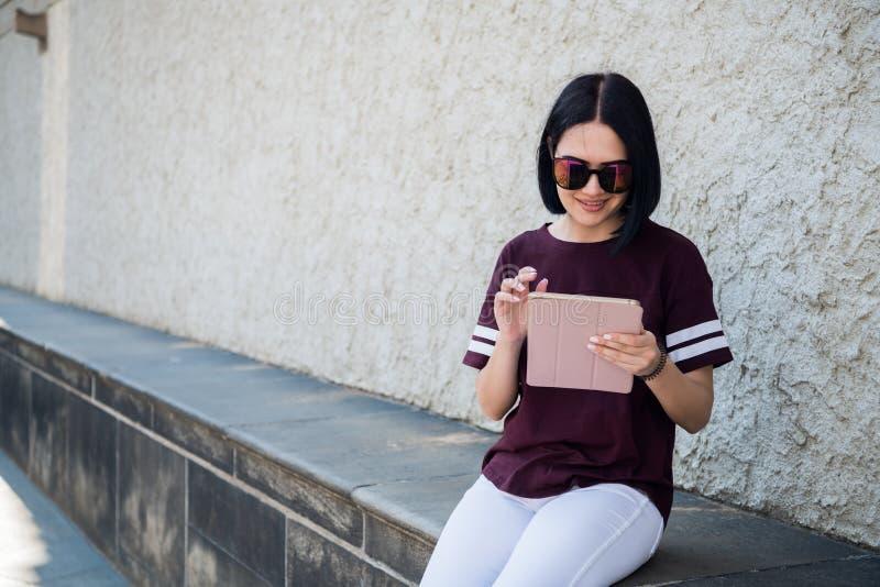 Mujer joven feliz emocionada que sostiene la tableta y que destaca el finger en el espacio de la copia mientras que se sienta en imagen de archivo libre de regalías
