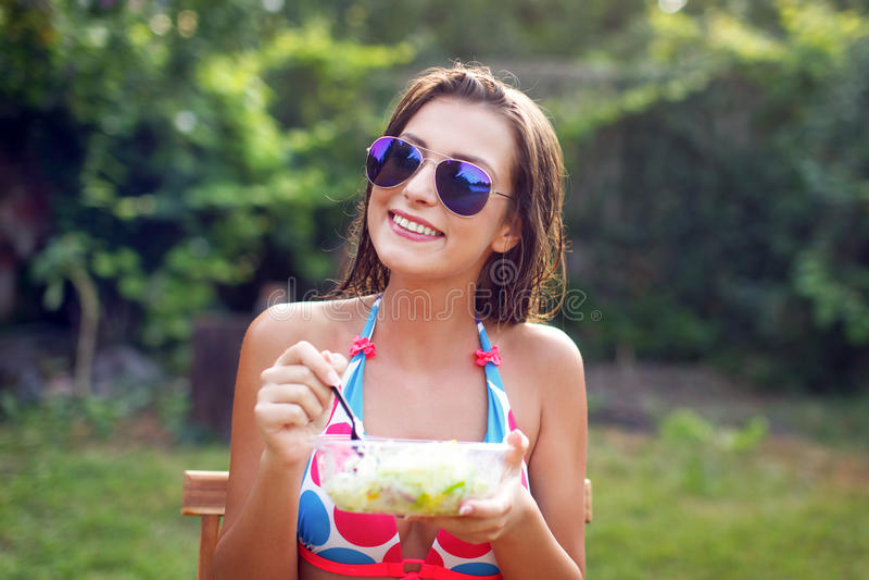 Mujer joven feliz en bikini que come la ensalada foto de archivo