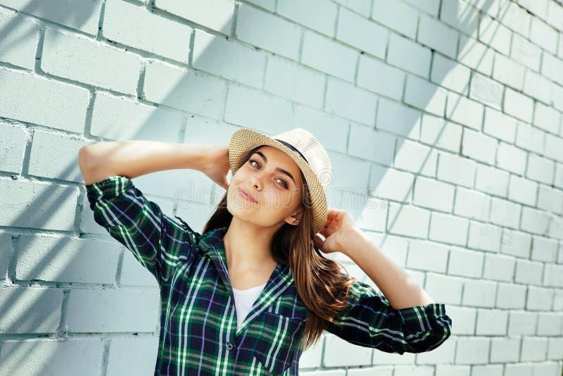 Mujer joven feliz en camisa del sombrero y de tela escocesa que sonríe, cerca de la pared de ladrillo azul foto de archivo