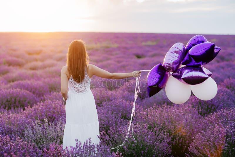 Mujer joven feliz en campo de la lavanda en la puesta del sol Concepto de la libertad foto de archivo