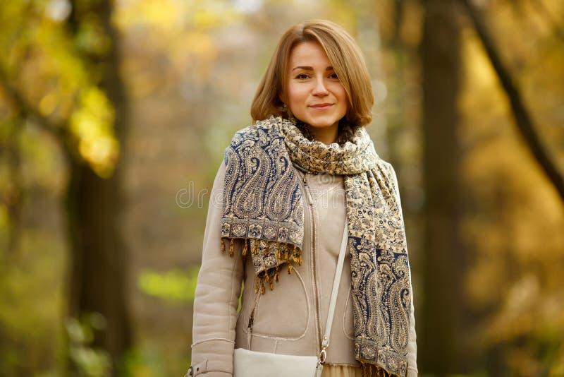 Mujer joven feliz en capa del otoño y tippet de moda al aire libre foto de archivo libre de regalías