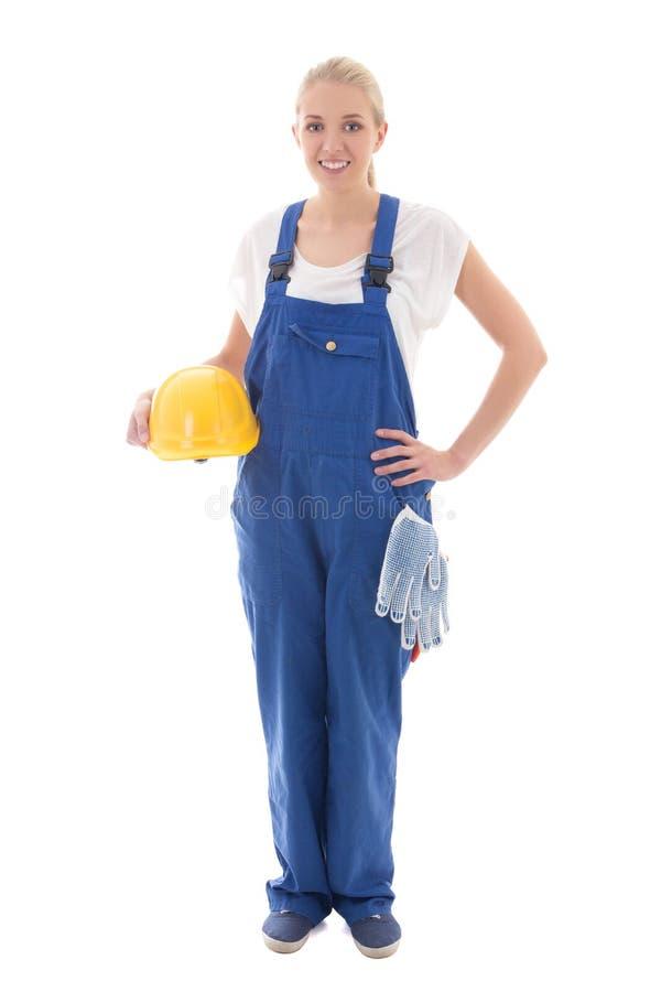Mujer joven feliz en casco uniforme del amarillo de la tenencia del constructor azul imagenes de archivo