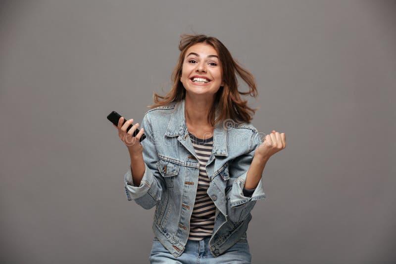 Mujer joven feliz en chaqueta de los vaqueros que aprieta sus puños en ganador fotografía de archivo libre de regalías