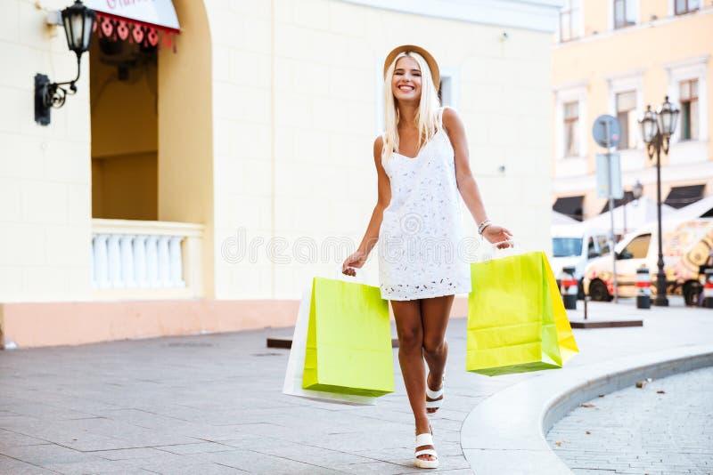 Mujer joven feliz en el sombrero que sostiene los panieres mientras que camina imágenes de archivo libres de regalías