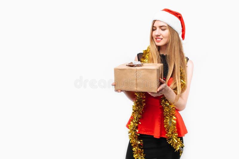 Mujer joven feliz en el sombrero y el vestido de santa, celebrando Año Nuevo foto de archivo