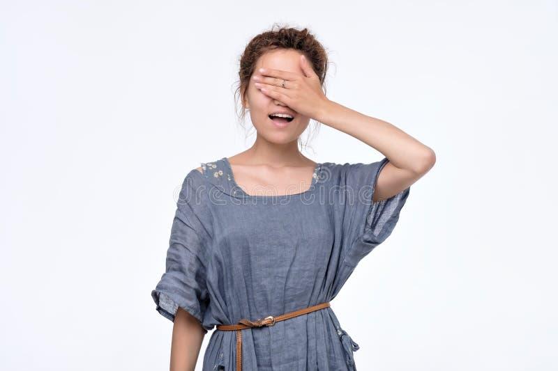 Mujer joven feliz en el vestido azul que cubre los ojos que esperan el regalo imágenes de archivo libres de regalías