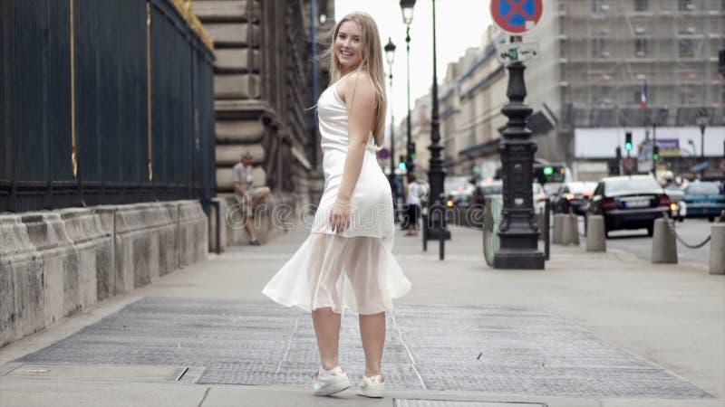 Mujer joven feliz en el vestido blanco que presenta en las calles de la ciudad del fondo acci?n Sonrisa rubia atractiva y present fotos de archivo