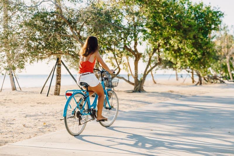 Mujer joven feliz en la bicicleta azul cerca del océano en la isla tropical imagen de archivo libre de regalías