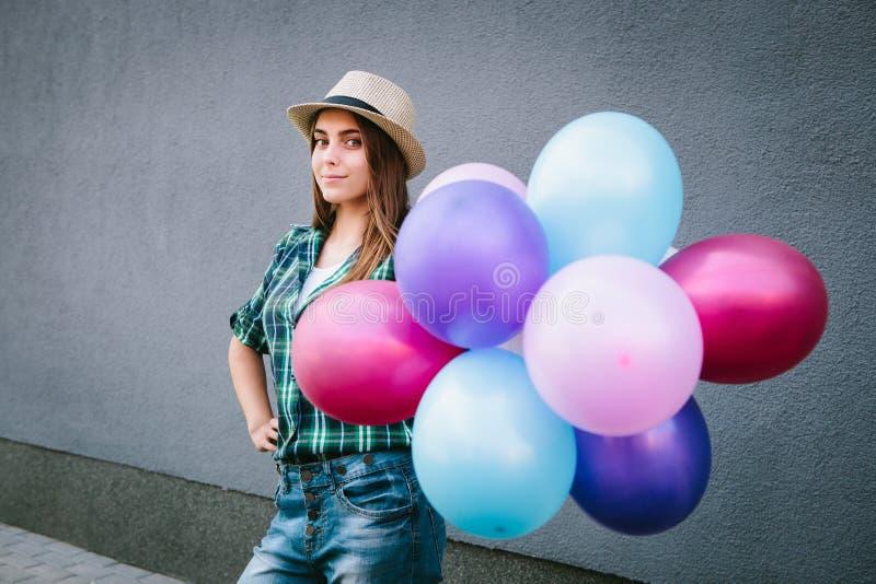 Mujer joven feliz en la camisa y el sombrero de tela escocesa que se colocan con los globos y la sonrisa fotografía de archivo libre de regalías